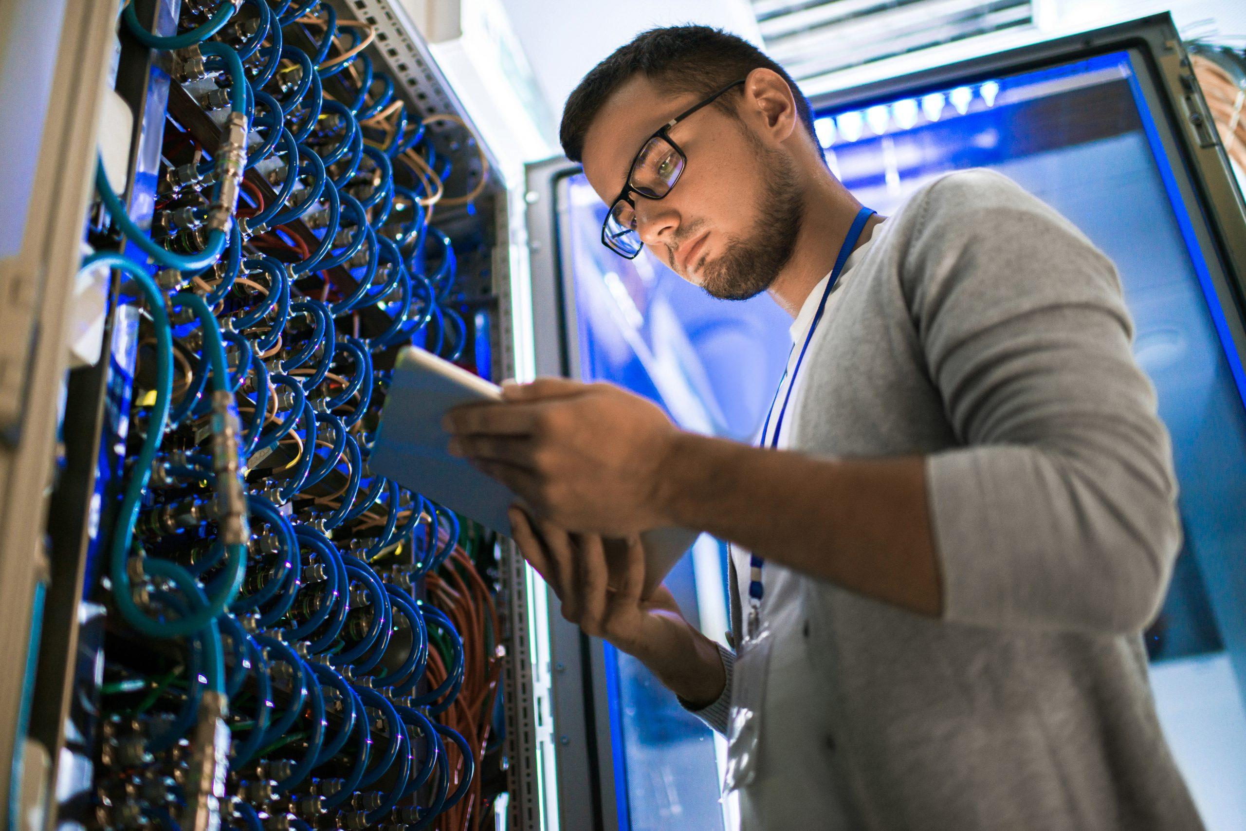 Junger Mann arbeitet im Serverraum