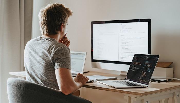 Junger Mann programmiert am PC