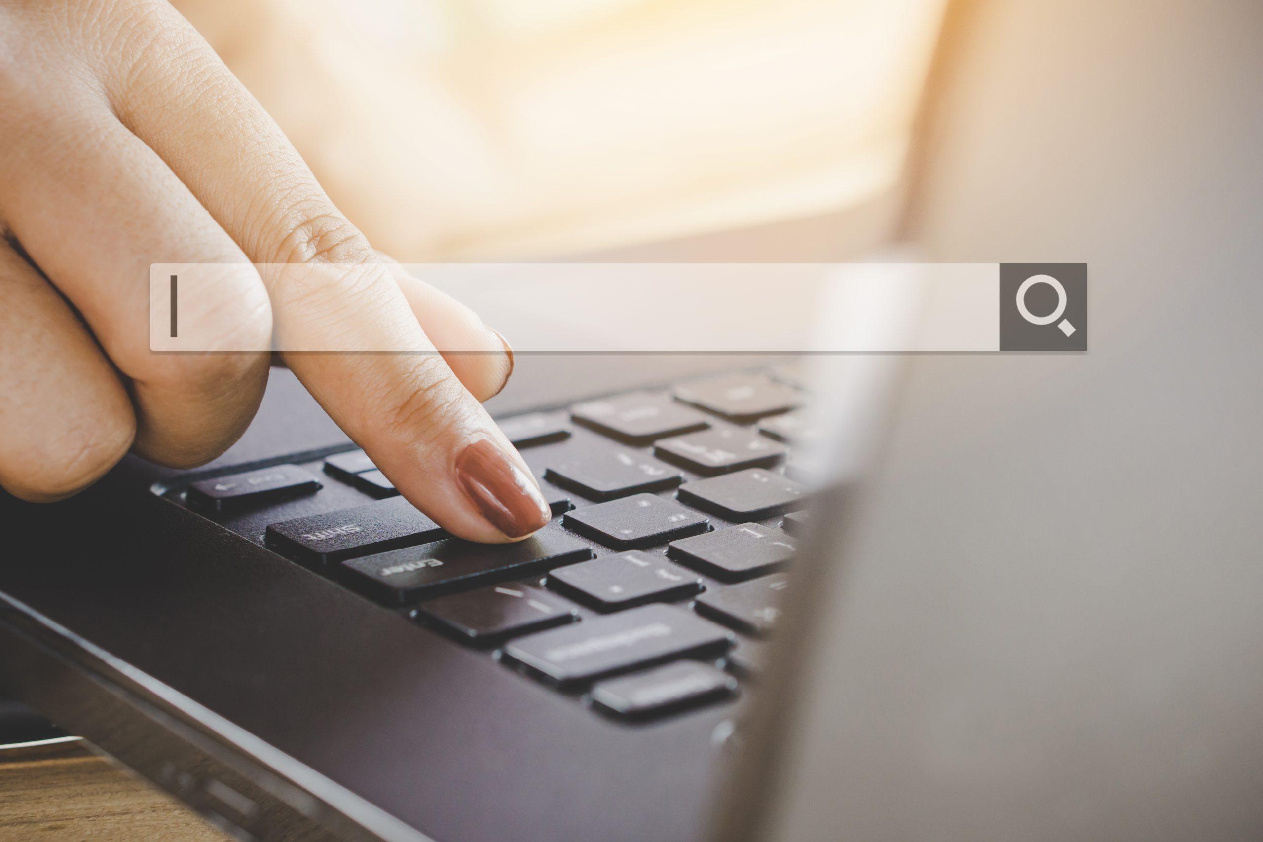 Frau tippt auf Laptop Tastatur Suchleiste offen