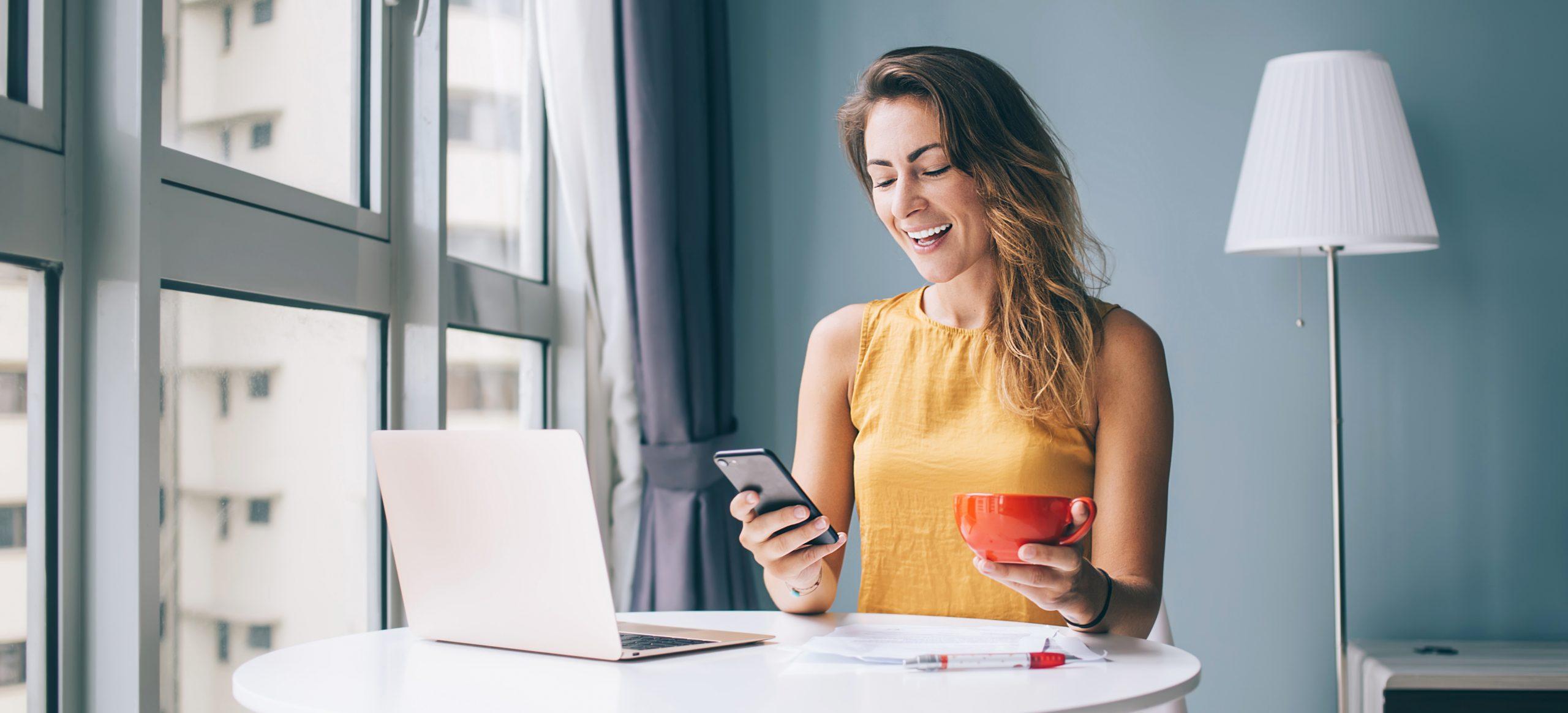 Dame schaut auf das Handy mit Caffè in der Hand, gegenüber einen Rechner